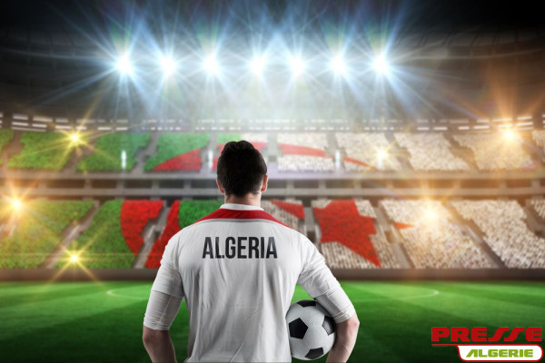 Algeria football player holding ball against stadium full of alg